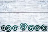 Mosquito repellent for outdoor: garden, summer house, picnic. Green spiral on grey wooden background top view copy space pattern poster