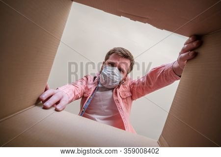 Man In A Medical Mask Unboxing Inside View A Delivered Box. Concept Of Paranoia And Hysteria Associa