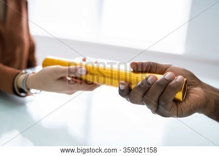 Passing Golden Relay Baton To Other Person