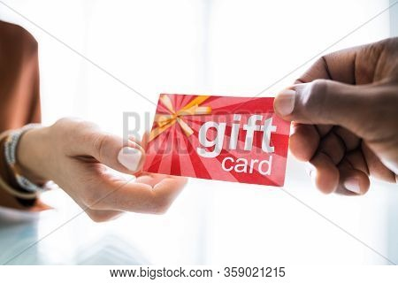 Close-up Of Two Businesspeople Hand Holding Red Gift Card