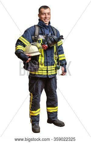 Young Smiling Firefighter In A Fireproof Uniform Stands And Looks At The Camera With A Helmet In His