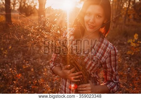 A Young Girl In A Joyful Mood Poses During The Sunset With Wildflowers.