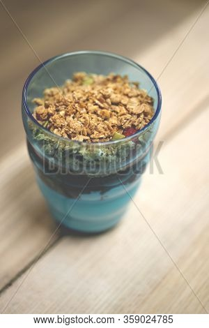 Vanilla Ice Cream Parfait With Granola Topping In A Clear Blue Tumbler