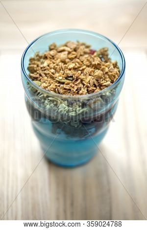 Granola-topped Vanilla Ice Cream Parfait In A Clear Blue Tumbler