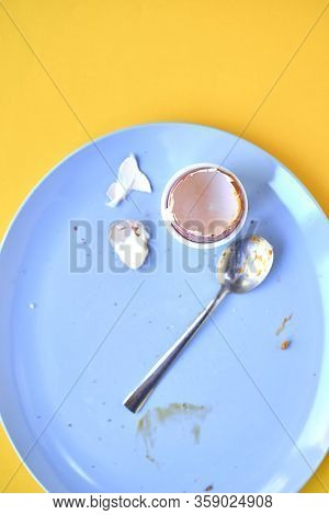 Dirty Blue Plate With Egg Shell In Egg Cup And A Used Spoon Over A Yellow Background
