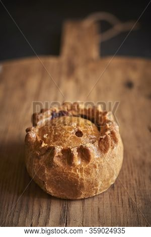 Cooked Meat Pie Isolated On A Wooden Oven Paddle With Copy Space