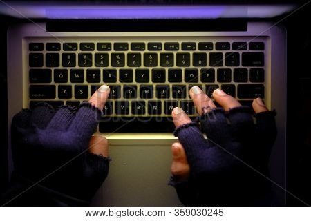 Hooded Hacker Stealing Data From Laptop At Night