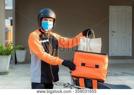 Delivery Asian Man Wear Protective Mask In Orange Uniform And Ready To Send Delivering Food Bag In F