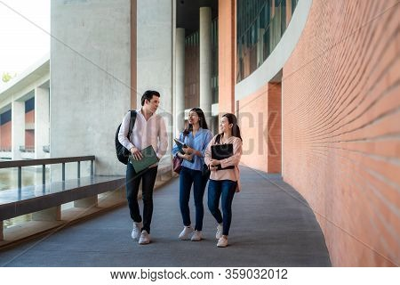 Asian Three Students Are Walking And Talking Together In University Hall During Break In University.