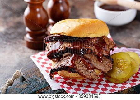 Smoked Barbeque Beef Brisket Sandwich With Pickles And Bbq Sauce