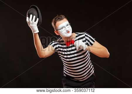 Portrait Of Male Mime Artist Performing, Isolated On Black Background. Man Raises His Hat And Touche