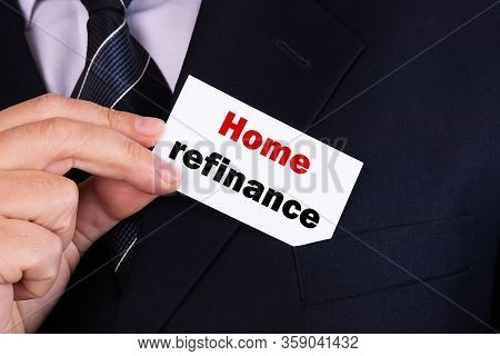 Businessman Putting A Card With Text Home Refinance In The Pocket