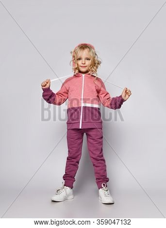 Beautiful Frolic Sly Smiling Curly Hair Blonde Kid Girl In Modern Fashion Pink Gray Sportswear Track