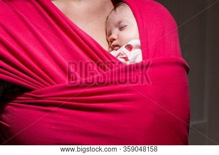 Mother Carrying Her Cute Baby Daughter In Sling. Newborn Baby Sleeping In A Sling, In The Embrace Of