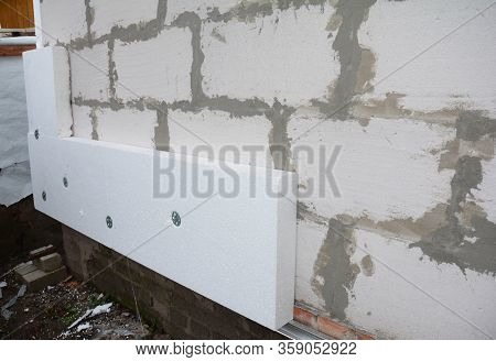 Installing Rigid Foam Board Insulation Using Screws With Large Washers On The House Wall Made From L
