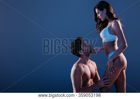 Sexy Girl In White Lingerie Touching Chin Of Shirtless Man Standing On Knees Isolated On Dark Blue
