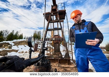 Serious Oil Man In Work Overalls And Helmet Holding Clipboard And Looking At Oil Pump Rocker-machine