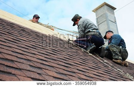 Kyiv, Ukraine - March, 29, 2020: Roofer Contractors Are Installing Dimensional Asphalt Shingles From