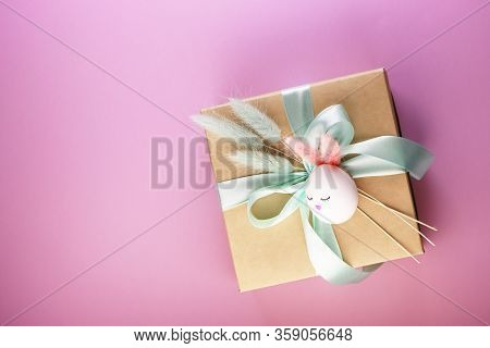 A Gift Box And A Flower On The Pink Table On Top. A Box Of Paper With A Blue Bow. Easter Egg In The