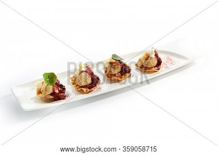 Turkey liver pate with berry sauce side view. Forcemeat paste snacks served with greenery and flowers. Delicious french cuisine dish on long white plate. Tasty appetizers with syrup