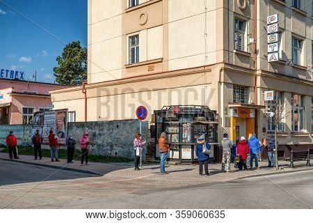 Ruzomberok, Slovakia - April 1, 2020: People With Face Mask Standing In Line In Front Of Shop