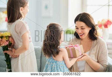 Happy mother's day! Children congratulating mom. Mum and daughters smiling and holding flowers and gift. Family holiday and togetherness.