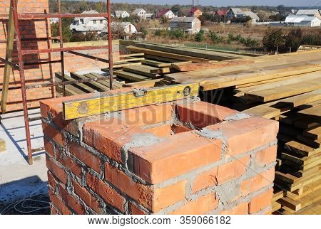 Building A Chimney Out Of Masonry, Noncombustible Red Bricks And Cement On The Rooftop Of A House.