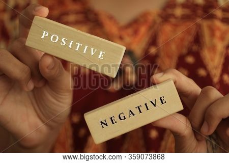 Young Woman Holding Antonym Word Sign Of Positive And Negative. Two Wooden Blocks In Hands With Life