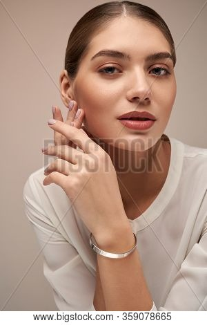 Crop Of Young Female Model With Perfect Makeup Presenting Minimalistic Silver Bracelet. Portrait Of