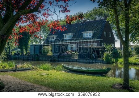 Zaan House And Boat With Small Canal And Trees And Red Leaves In Zaanse Schans Amsterdam.