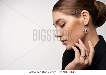 Close Up Portrait Of Young Beautiful Brunette Female Model Presenting Golden And Silver Earrings And