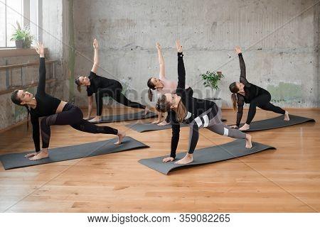 Group Of Five Girls Practicing Yoga In Fitness Hall, Doing Utthita Parsvakonasana Exercise On Mat, S