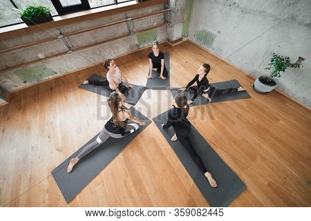 From Above View Of Group Of Attractive Girls In Sportswear Practicing Semi Twine In Fitness Hall. Yo