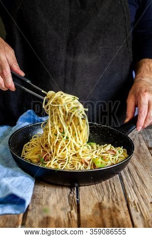 A Chef Preparing Vegetables And Bacon To Cook Pasta