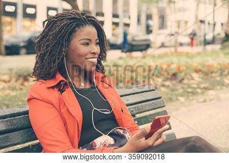 Smiling Woman In Earphones Using Smartphone. Content Young African American Woman Listening Music In