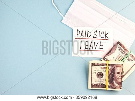 White Medical Mask, Money And Paid Sick Leave Text On A Blue Background. Concept Of Payment For Sick