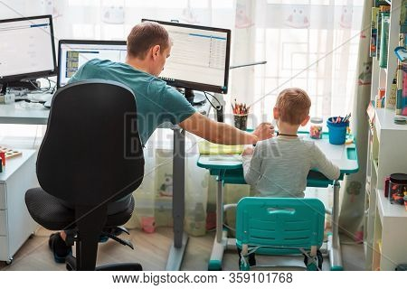 Father With Kid Working From Home During Quarantine. Stay At Home, Work From Home Concept During Cor