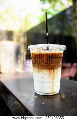 A Close Up View Of Iced Caramel Macchiato On A Rusty Table