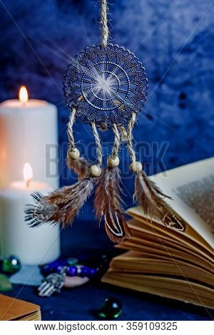 Dreamcatcher Amulet Feng Shui. Dream Catcher From Metal And Feathers Against The Background Of Burni
