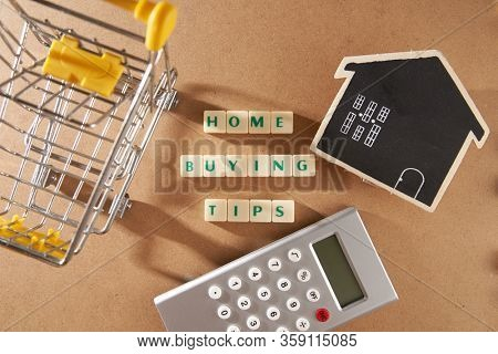 word home buying tips on square blocks with mini shopping cart model house and calculator