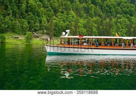 Upper Bavaria, Germany - May 27, 2019: An Excursion Boat On The Königssee Glides Past A Rustic Shelt