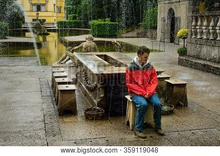 Salzburg, Austria - May 28, 2019: A Tour Group Volunteer Sits On The Archbishop Seat As The Trick Fo