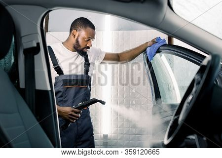 Car Detailing, Steam Cleaning Concept. Handsome African Man In Overalls And T-shirt, Worker Of Car W