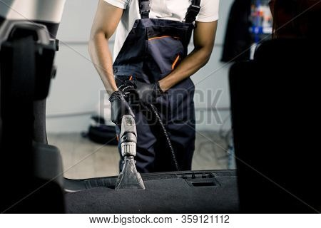 Professional Cleaning Of Car Interior By Wet Vacuum Machine. Clopped Image Of Male African Auto Serv