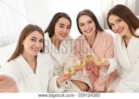 Beautiful Young Ladies With Glasses Of Wine Taking Selfie At Pamper Party Indoors. Woman's Day