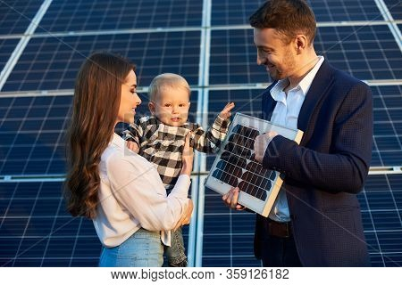 Bussinesman Stands In His Hands With A Solar Battery Near Him A Beautiful Girl With A Child In Her A