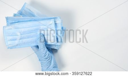 Doctor, Nurse Or Pharmacist In Medical Gloves Holding A Stack Of Protective Face Mask. Possible Conc