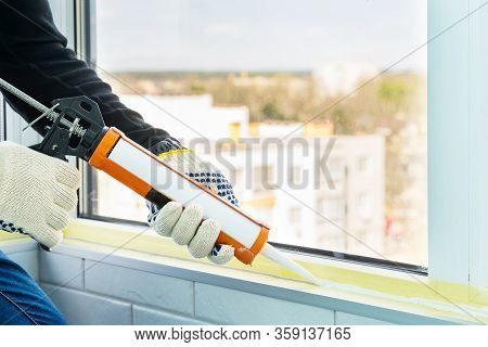 Contractor Hand Holding Glue Gun With Silicone To Repair Tile And Window. Installation Or Renovation
