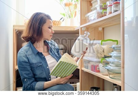 Woman In Pantry With Groceries, Wooden Shelf For Food Storage In Kitchen, Female With Recipe Book Ta
