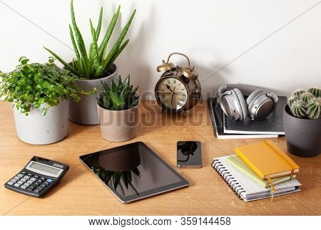 home office desk with tablet computer smartphone notebook houseplants, working space at home